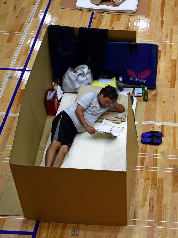 Penduduk setempat beristirahat di pusat evakuasi dengan kotak kardus untuk menjaga jarak di sebuah gimnasium kota Yatsushiro di prefektur Kumamoto, Jepang, Senin (6/7/2020). Hujan deras menghambat operasi pencarian dan penyelamatan korban banjir dan tanah longsor di Kumamoto. (Charly TRIBALLEAU/AFP)