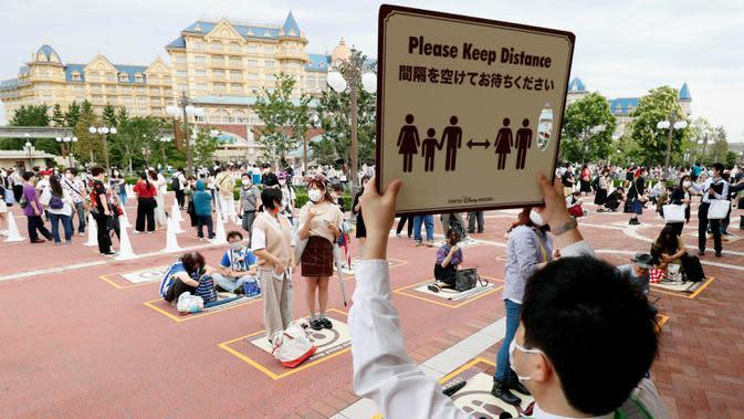 Pengunjung mengenakan masker saat menjaga jarak untuk antre memasuki Tokyo Disneyland di Urayasu, dekat Tokyo, Rabu (1/7/2020). Tokyo Disneyland dibuka kembali untuk pertama kalinya dalam empat bulan setelah sempat ditutup karena penyebaran Covid-19. (Kyodo News via AP)