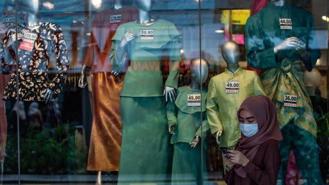 Seorang wanita mengenakan masker sebagai tindakan pencegahan Covid-19 melihat ponselnya di depan sebuah toko yang menjual pakaian budaya Malaysia yang disebut Baju Melayu dan Baju Kurung menjelang Idul Fitri yang menandai berakhirnya bulan suci Ramadan di Kuala Lumpur (13/5/2020). (AFP/Mohd Rasfan)
