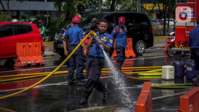 Personil pemadam kebakaran membersihkan tumpah oli di Jalan Veteran depan Gedung Krida Bakti, Jakarta, Kamis (16/1/2020). Sudin Damkar Jakarta Pusat mengerahkan 2 unit mobil damkar dan 10 personil untuk membantu pembersihan bagian jalan yang terkena tumpahan oli. (Liputan6.com/Faizal Fanani)