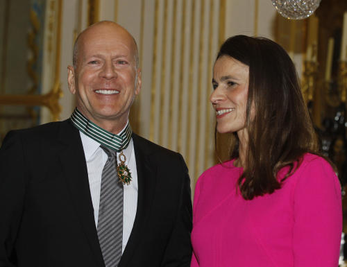 American movie star Bruce Willis smiles after being awarded with the medal of Commander of Arts and Letters by French culture minister Aurelie Filippetti, right, in Paris, Monday Feb. 11, 2013.(AP Photo/Remy de la Mauviniere)