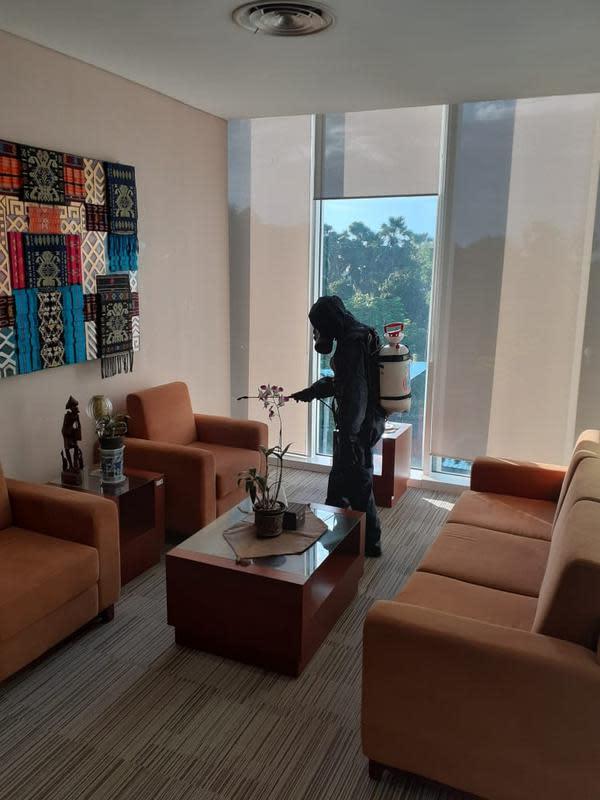Petugas menyemprot cairan disinfektan di kantor BI NTT. (Liputan6.com/Ola Keda)