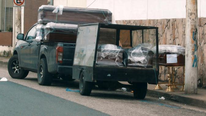 Sebuah truk mengangkut sejumlah peti mati di trotoar luar rumah sakit di Guayaquil, Ekuador, Rabu (1/4/2020). Warga Guayaquil mengungkapkan kemarahan mereka atas cara pemerintah menangani korban meninggal karena virus corona COVID-19. (Enrique ORTIZ/AFPTV/AFP)
