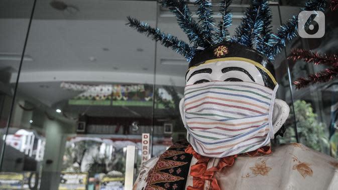 Ondel-ondel mengenakan masker terpajang di depan Kantor Kecamatan Kelapa Gading, Jakarta, Senin (21/9/2020). Kantor Kecamatan Kelapa Gading ditutup sementara selama 3 hari hingga Rabu (23/9) mendatang, pasca meninggalnya Camat Kelapa Gading, M Harmawan akibat COVID-19. (merdeka.com/Iqbal Nugroho)