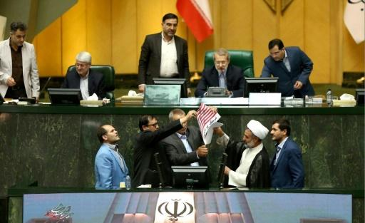 A handout picture provided by the Iranian Parliament on May 9, 2018 shows Iranian MPs preparing to burn a US flag in the parliament in Tehran