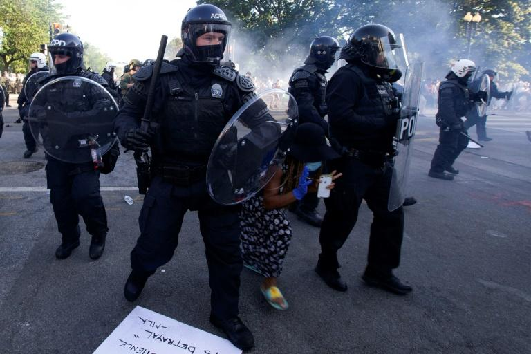 A demonstrator tries to pass between police wearing riot gear as they push back protesters outside the White House on June 1, 2020