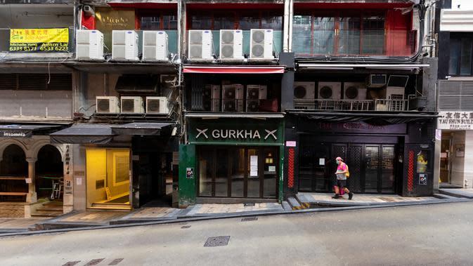 Seorang pengantar barang berjalan di jalan sepi di kawasan hiburan malam Lan Kwai Fong, Hong Kong (4/4/2020). Kebijakan pemerintah Hong Kong itu membuat gemerlap hiburan malam di Lan Kwai Fong meredup seketika. (AFP/May James)
