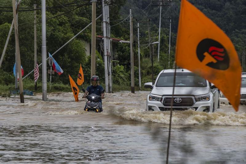 Motorists brave the flood waters on Jalan Datuk Panglima Banting in Penampang, Sabah September 15, 2020. — Picture by Firdaus Latif