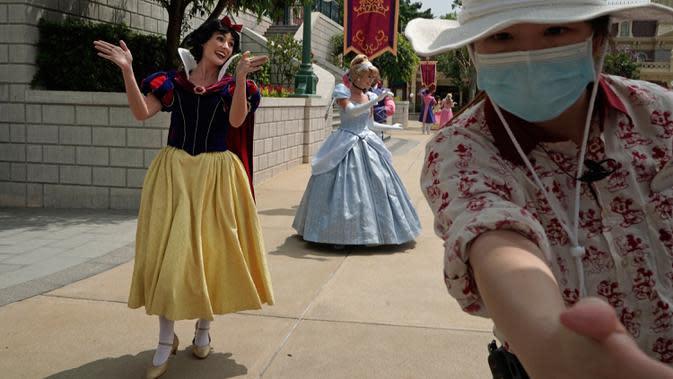 Seorang karyawan menjauhkan pengunjung dari artis di Disneyland Hong Kong pada Jumat (25/9/2020). Setelah dibuka dan tutup kembali, Disneyland Hong Kong dibuka kembali untuk wisatawan. (AP Photo/Kin Cheung)