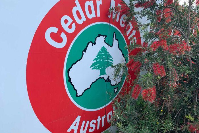A close-up photograph of the Cedar Meats Australia logo, next to a bottlebrush tree.