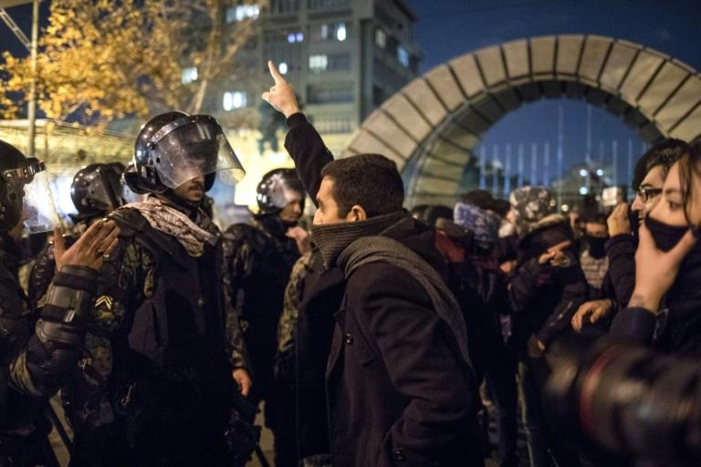 A man confronts riot police during a demonstration outside Tehran's Amir Kabir University after Iran admitted to having shot down a Ukrainian passenger jet by mistake