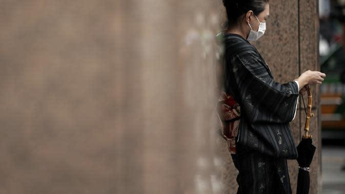 Seorang wanita berkimono tradisional Jepang yang mengenakan masker untuk membantu mencegah penyebaran virus corona berjalan di Tokyo, Kamis (10/9/2020). Ibu kota Jepang itu mengonfirmasi lebih dari 270 kasus virus corona pada Kamis. (AP Photo / Eugene Hoshiko)