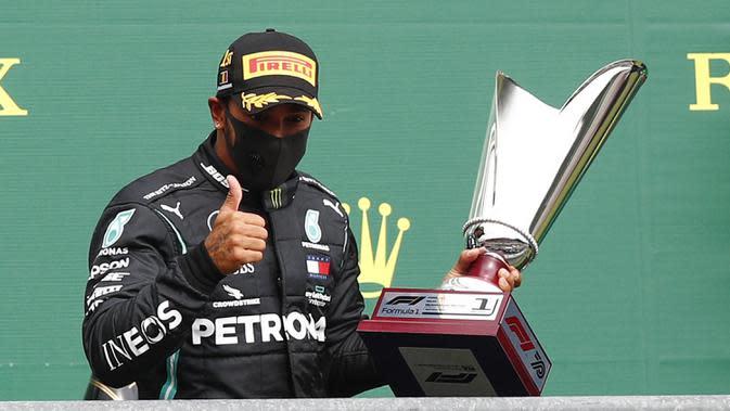 Pembalap Mercedes Lewis Hamilton mengangkat trofi usai menempati posisi pertama Formula 1 Grand Prix di Spa-Francorchamps, Spa, Belgia, Minggu (30/8/2020). Posisi kedua dan ketiga diisi pembalap Mercedes Valtteri Bottas serta pembalap Red Bull Max Verstappen. (Francois Lenoir/Pool Photo via AP)