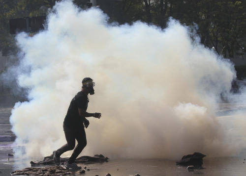 A mased anti-government protester runs away from a tear gas canister fired by riot police at a gymnasium in Bangkok, Thailand, Thursday, Dec. 26, 2013. Protesters trying to halt preparations for elections fought running battles with police in the Thai capital on Thursday, escalating their campaign to topple the country's beleaguered government. (AP photo/Sakchai Lalit)