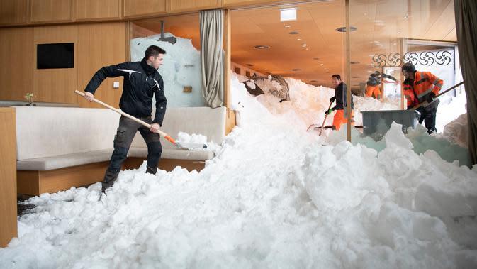 Petugas membersihkan longsoran salju yang masuk ke dalam Hotel Saentis di Schwaegalp, Swiss, Jumat (11/1). Polisi mengatakan tiga orang terluka dalam insiden tersebut. (Gian Ehrenzeller/Keystone via AP)