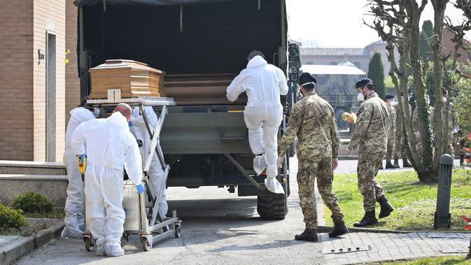 Petugas membawa peti mati berisi jasad korban virus corona COVID-19 yang diturunkan dari truk militer di pemakaman Ferrara, Italia, Sabtu (21/3/2020). Dari mereka yang awalnya terinfeksi COVID-19 secara nasional, 6.072 orang telah dinyatakan pulih sepenuhnya. (Massimo Paolone/LaPresse via AP)
