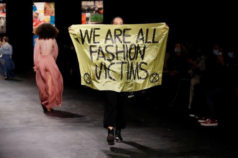Extinction Rebellion protester walks runway at Dior in Paris