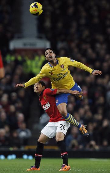 Manchester United's Kagawa challenges Arsenal's Arteta during their English Premier League soccer match in Manchester