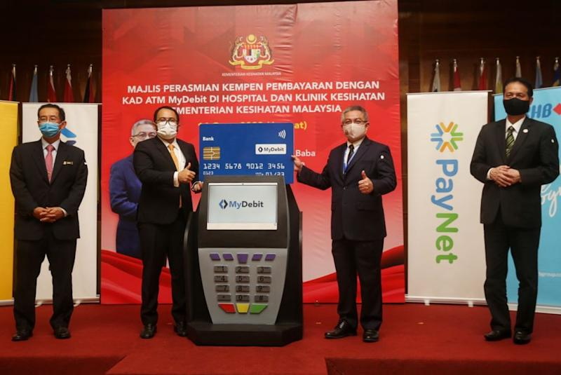 Datuk Seri Dr Adham Baba (second from right) attends a campaign on the use of MyDebit ATM cards at government hospitals and clinics in Putrajaya August 14, 2020. — Picture by Choo Choy May