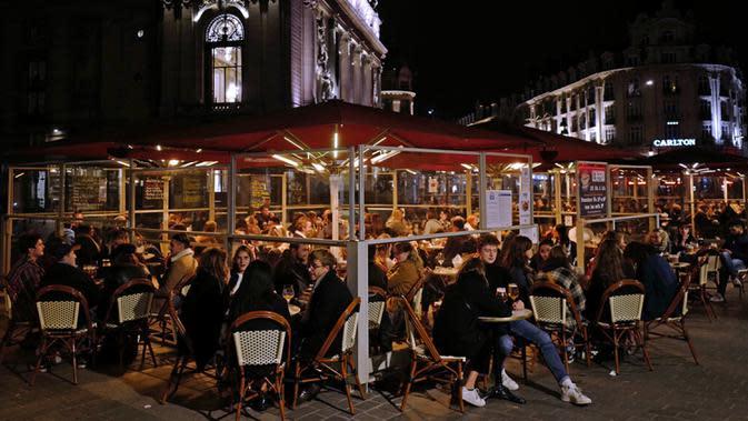 Orang-orang menikmati minuman di teras restoran di Lille, Prancis, Jumat (16/10/2020). Prancis mengerahkan 12.000 polisi untuk memberlakukan jam malam baru mulai Jumat malam hingga bulan depan untuk memperlambat penyebaran COVID-19. (AP Photo/Michel Spingler)