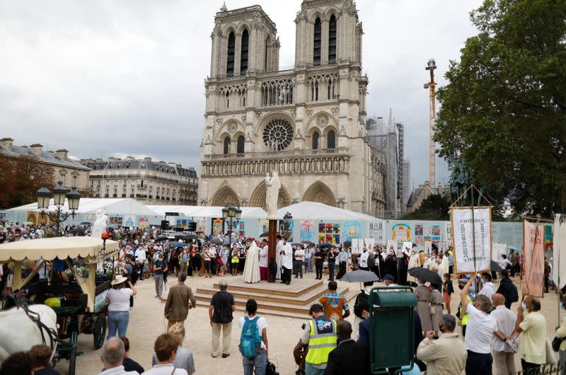 Wearing masks, French pilgrims send a message of hope ahead of religious feast