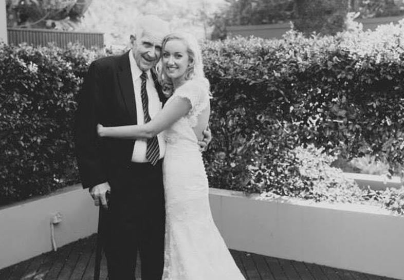Queensland woman Sian is shown on her wedding day posing in a garden with her grandfather.
