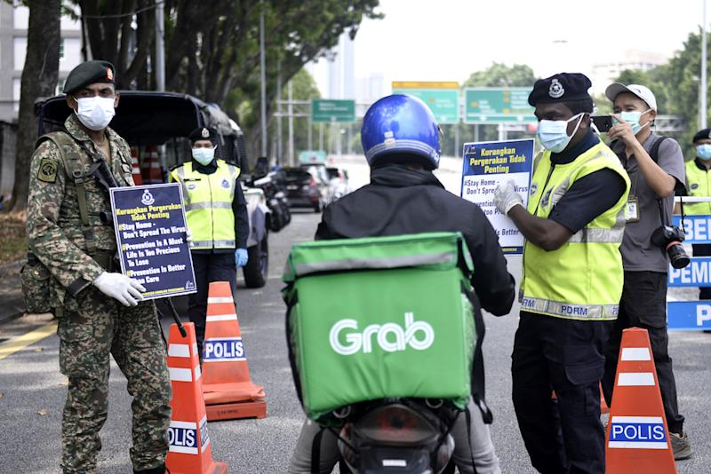 Soldiers and police officers conducting checks at a roadblock on day five of the movement control order (MCO) in Sri Hartamas March 22,2020. — Picture by Miera Zulyana