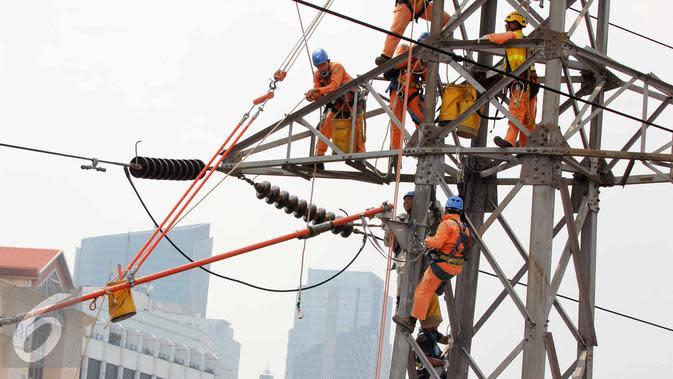Petugas PLN memperbaiki Menara Sutet di Jalan Asia Afrika, Jakarta, Rabu (12/8/2015). Pekerjaan tersebut mengandung resiko besar karena jaringan listrik masih dipelihara tanpa dipadamkan. (Liputan6.com/Helmi Afandi)