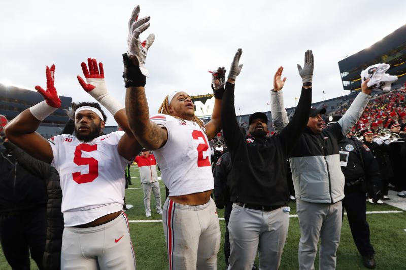 FILE - In this Nov. 30, 2019, file photo, Ohio State's Baron Browning (5), Chase Young (2), linebackers coach Al Washington and head coach Ryan Day celebrate after a victory over Michigan in an NCAA college football game in Ann Arbor, Mich. Across the country universities have begun the process of playing through a pandemic. As athletes return to campus, what are they signing up for? Ohio State and Missouri have pledges they are requiring athletes or their parents sign before the players can take part in voluntary workouts at team facilities. (AP Photo/Paul Sancya, File)