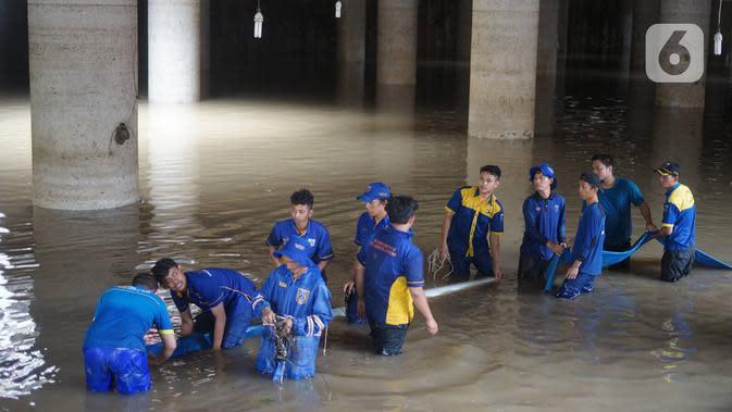 Petugas memasang pompa penyedot air di banjir yang menggenangi underpass Kemayoran, Jakarta, Senin (3/2/2020). Curah hujan tinggi menyebabkan banjir yang menggenangi kawasan tersebut lama surut sehingga menutup arus lalu lintas. (Liputan6.com/Immanuel Antonius)