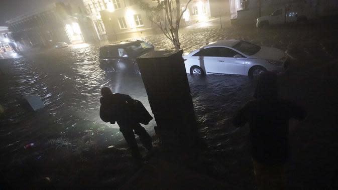 Orang-orang menggunakan senter saat mereka berjalan di jalan-jalan yang banjir untuk mencari kendaraan mereka di Pensacola, Florida, Rabu (16/9/2020). Badai Sally membuat pendaratan hari Rabu di dekat Gulf Shores, Alabama, sebagai badai Kategori 2. (AP Photo/Gerald Herbert)