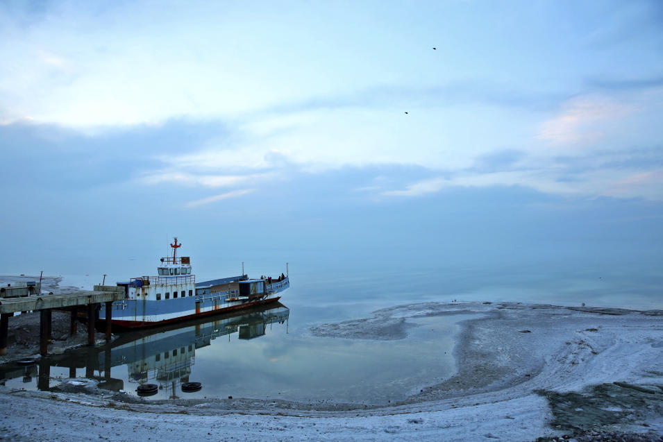 In this picture taken on Saturday, Feb. 15, 2014, an abandoned ship is stuck in a dock on Lake Oroumieh, in northwestern Iran. Lake Oroumieh, one of the biggest saltwater lakes on Earth, has shrunk more than 80 percent to 1,000 square kilometers (nearly 400 square miles) in the past decade. Rescuing the lake in northwestern Iran, near the Turkish border, was one of Iranian President, Hassan Rouhani's, campaign promises, and his new cabinet promptly decided to form a team to invite scholars to help find solutions. (AP Photo/Ebrahim Noroozi)