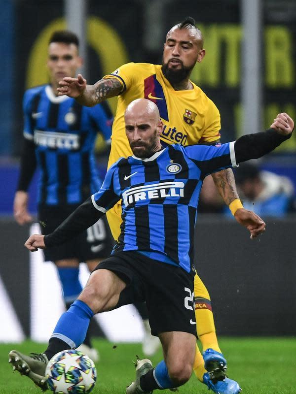 Gelandang Barcelona, Arturo Vidal berusaha merebut bola dari gelandang Inter Milan, Borja Valero pada pertandingan Grup F Liga Champions di stadion San Siro di Milan pada 10 Desember 2019. (AFP/Miguel Medina)
