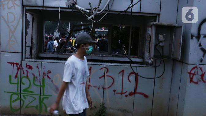 Seorang anak muda melintasi Pos Polisi yang dirusak massa di kawasan Gondangdia, Jakarta, Kamis (8/10/2020). Aksi anarkis massa dilakukan saat berunjuk rasa menentang disahkan Omnibus Law UU Cipta Kerja. (Liputan6.com/Helmi Fithriansyah)