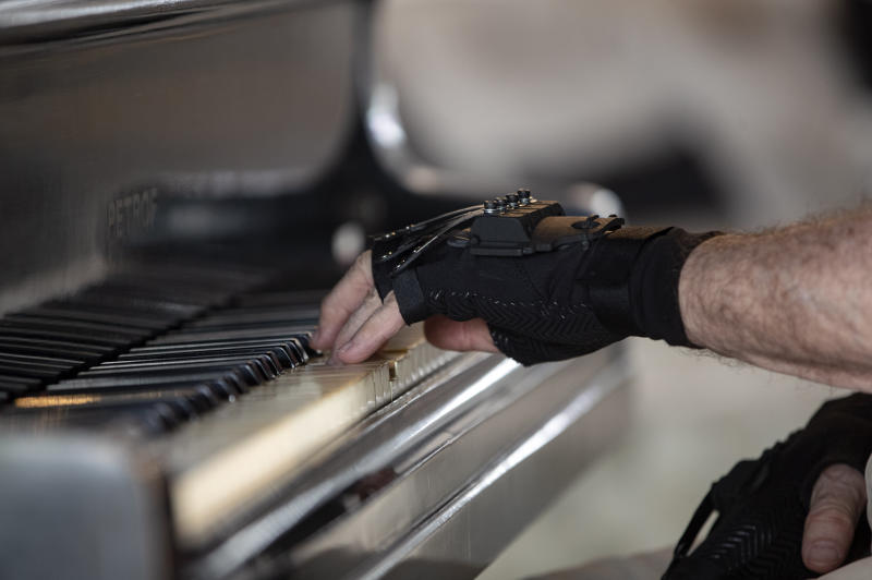 Brazilian pianist Joao Carlos Martins plays the piano wearing bionic gloves at his home in Sao Paulo, Brazil, Wednesday, Jan. 22, 2020. Martins, 79, was for decades Brazil's most acclaimed pianist, but an accident an a degenerative disease forced him to stop playing with both hands since 1998. That changed a few months ago when a new friend came to him with a pair bionic gloves that suit him perfectly. He can now play again with nine out of ten fingers. (AP Photo/Andre Penner)