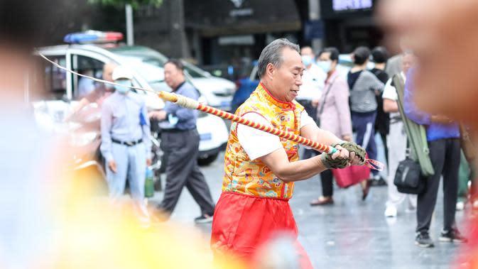Pria berusia 71 tahun yang merupakan anggota Klub Gasing Kylin Guiyang memainkan sebuah gasing raksasa di Lapangan Jiaxiulou di Guiyang, Provinsi Guizhou, China barat daya, (15/5/2020). (Xinhua/Ou Dongqu)