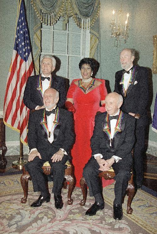 File- This 1994 file photo shows actor Kirk Douglas, standing from left, singer Aretha Franklin, singer Peter Seeger and seated from left, director Harold Prince and composer Morton Gould pose for photographers on Saturday, Dec. 3, 1994 following a dinner at the State Department in Washington. The dinner was to honor them as recipients of the Kennedy Center Honors of 1994. The American troubadour, folk singer and activist Seeger died Monday Jan. 27, 2014, at age 94. (AP Photo/Doug Mills, File)