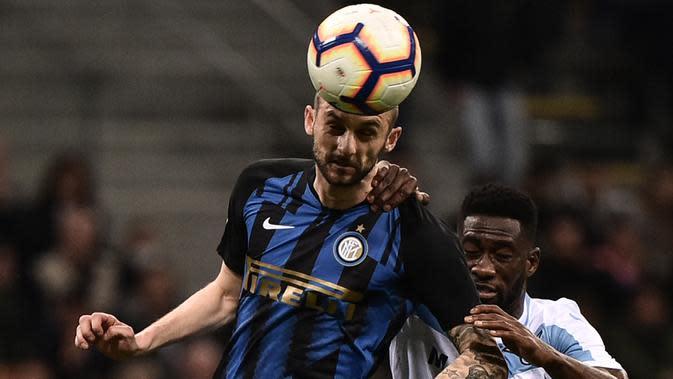 Bek Lazio, Bastos, duel udara dengan gelandang Inter Milan, Marcelo Brozovic, pada laga Serie A di Stadion Giuseppe Meazza, Minggu (31/3). Inter Milan takluk 0-1 dari Lazio. (AFP/Marco Bertorello)