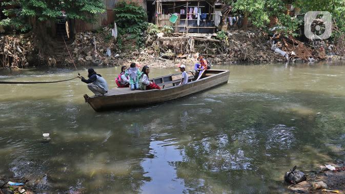 Sejumlah murid SD naik perahu di Sungai Ciliwung, Kampung Tanah Rendah, Jakarta, Jumat (15/11/2019). Pembataalan pembebasan 118 bidang tanah tersebut menyebabkan proyek normalisasi Sungai Ciliwung yang telah berhenti sejak tiga tahun yang lalu menjadi terhambat. (Liputan6.com/Herman Zakharia)