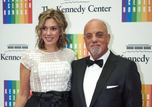 FILE - In this Dec. 7, 2013 file photo, Kennedy Center Honoree Billy Joel,right, and Alexis Roderick arrive at the Kennedy Center Honors gala dinner in Washington. Joel married girlfriend Alexis Roderick in a surprise ceremony at the couple's annual July 4 party. The singer's spokeswoman Claire Mercuri says New York Gov. Andre Cuomo presided over Saturday's nuptials at Joel's Long Island estate. (AP Photo/Kevin Wolf, File)