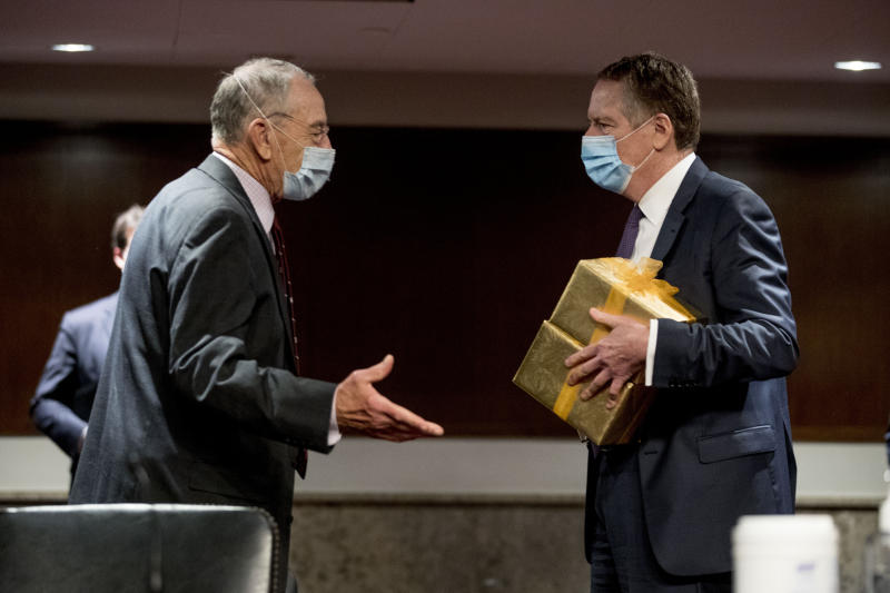 U.S. Trade Representative Robert Lighthizer arrives with gifts for Chairman Sen. Chuck Grassley, R-Iowa, left, and Ranking Member Sen. Ron Wyden, D-Ore., as he arrives at a Senate Finance Committee hearing on U.S. trade on Capitol Hill, Wednesday, June 17, 2020, in Washington. (AP Photo/Andrew Harnik, Pool)