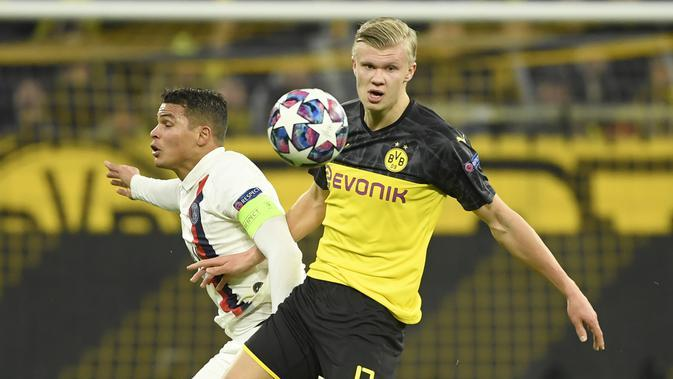 Striker Borussia Dortmund, Erling Braut Haaland, berebut bola dengan bek Paris Saint-Germain, Thiago Silva, pada leg pertama 16 besar Liga Champions di Signal Iduna Park, Dortmund, Rabu (19/2) dini hari WIB. Dortmund menang 2-1 atas PSG.(AFP/Ina Fassbender)