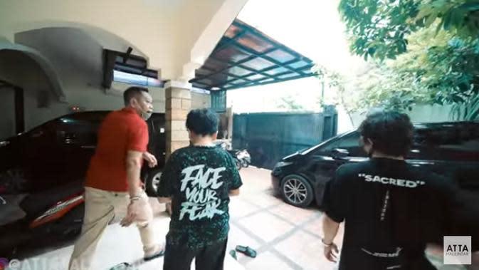 Tukul juga mengajakk Atta Halilintar untuk melihat garasi rumah baru. Terlihat dalam garasi tersebut ada beberapa mobil Tukul dan anak-anaknya. Selain memperlihatkan sisi luar, ia juga memperlihatkan sisi dalamnya. (Youtube/ Atta Halilintar)