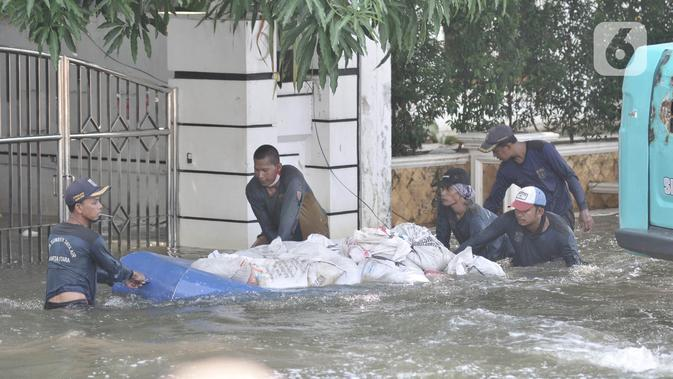 Petugas Sumber Daya Air (SDA) menggunakan perahu karet saat membawa karung pasir di Kompleks Perumahan Pantai Mutiara, Pluit, Jakarta, Minggu (7/6/2020). (Liputan6.com/Iqbal S. Nugroho)