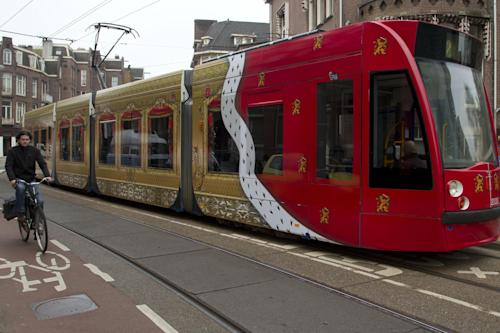 A tram decorated with amongst others the Dutch flag, impressions of the Queen's Golden Carriage, and a Royal Cape, makes its way through Amsterdam, Netherlands, Wednesday April 17, 2013. The tram is specially decorated to commemorate the April 30, 2013 abdication of Queen Beatrix, who will step down leaving the monarchy to her son Crown Prince Willem Alexander. (AP Photo/Peter Dejong)