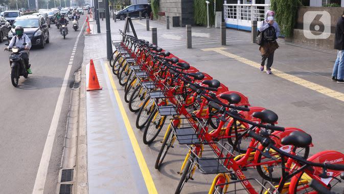 Pejalan kaki melintas di dekat deretan sepeda untuk layanan bike sharing atau penyewaan sepeda di Kawasan Jakarta, Jumat (3/7/2020). Layanan bike sharing yang bertujuan untuk mengurangi penggunaan kendaraan bermotor ini terbagi dalam 6 titik lokasi di Jakarta. (Liputan6.com/Angga Yuniar)