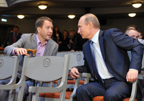 FILE- In this Sept. 15, 2011, file photo, then-Russian Prime Minister Vladimir Putin, right, speaks with Director of the Theater of Nations Yevgeny Mironov as he visits the Theater of Nations in Moscow, Russia. An artists' spat over President Vladimir Putin and his adoption ban joins a long tradition in Russian politics. At the core of the argument today is a question about what an artist's role should be in Putin's Russia: attracting generous state funding for bigger and better artistic projects, or challenging the political system in a way most ordinary citizens cannot afford to do. (AP Photo/RIA Novosti, Alexei Nikolsky, Pool, File)