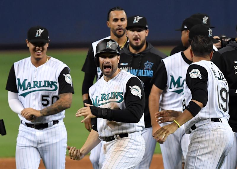 Jul 26, 2019; Miami, FL, USA; Miami Marlins third baseman Neil Walker (18) celebrates with teammates after scoring the winning run on a sacrifice fly by Marlins left fielder Harold Ramirez (not pictured) against the Arizona Diamondbacks at Marlins Park. Mandatory Credit: Steve Mitchell-USA TODAY Sports