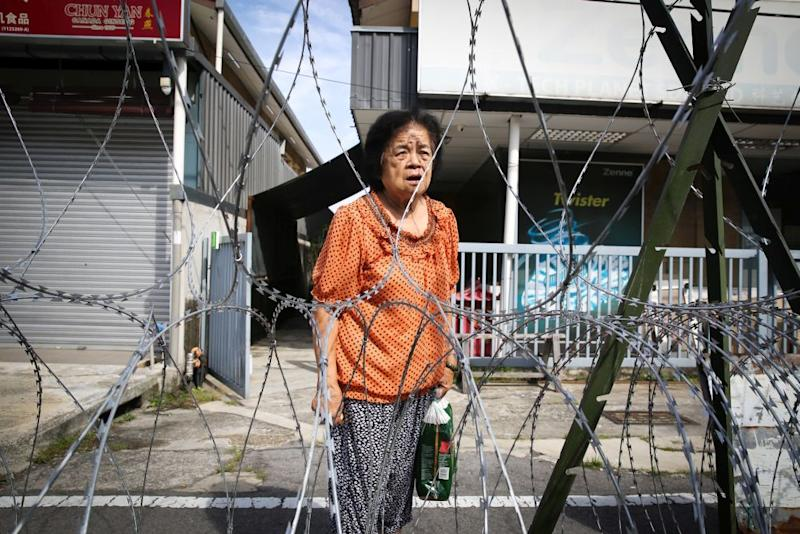 Retiree Wong Ai Kwok speaks to Malay Mail from beyond the barbed wire fencing at Petaling Jaya Old Town during the enhanced movement control order May 12, 2020. — Picture by Yusof Mat Isa