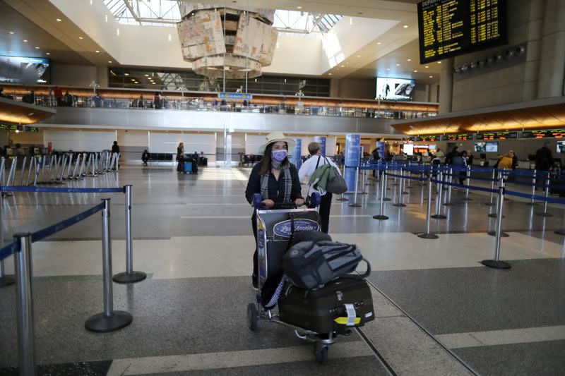 FILE PHOTO: A woman walks through the empty international terminal at LAX airport in Los Angeles
